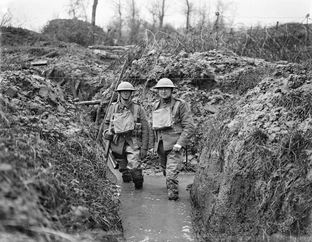 Two soldiers with water up to their ankles in a trench